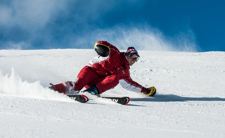 A man riding a snowboard down a snow covered slope