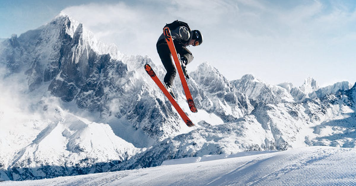 A man jumping in the air on a snow covered mountain