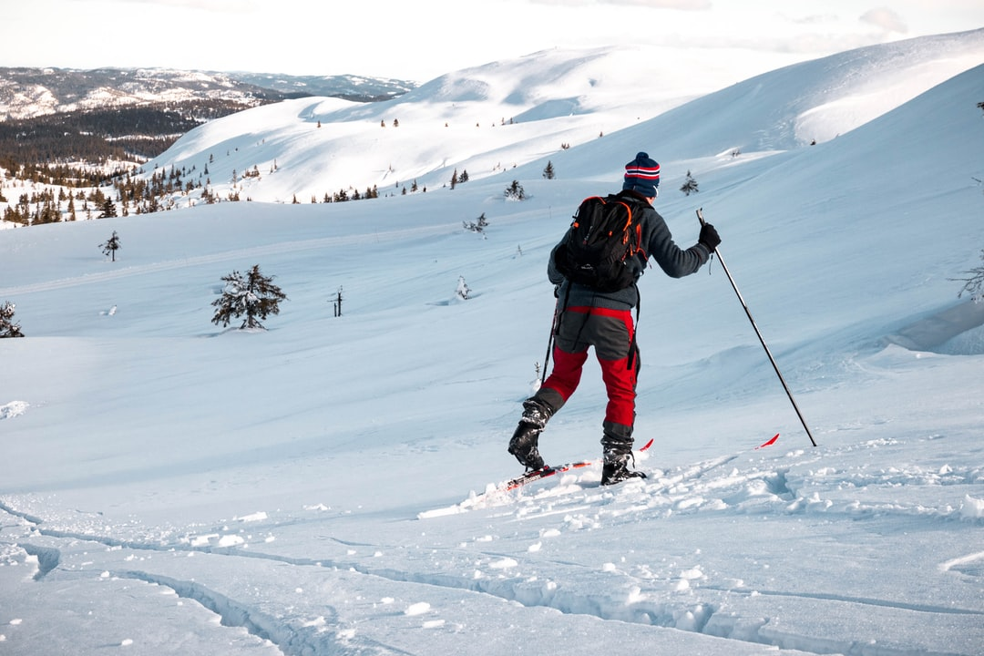 A man riding skis down a snow covered slope