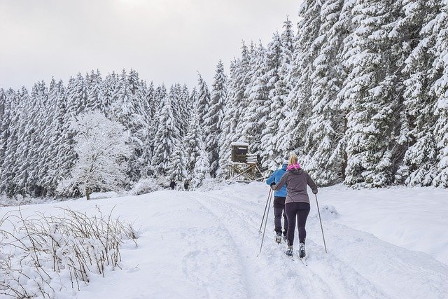 A person is cross country skiing on a snow covered slope